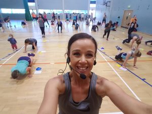 girl smiling taking a selfie at a fitness class in a large sports hall with blue walls
