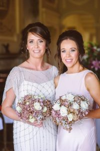 Donna Dunne Fitness at her sisters weddign both girls holding a bunch of flowers