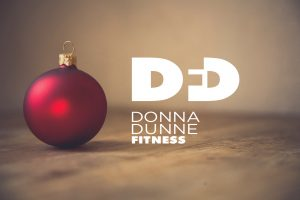 red Christmas decoration on a wooden table with donna dunne fitness logo embedded in the image