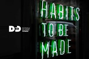 neon sign which says habits to be made
