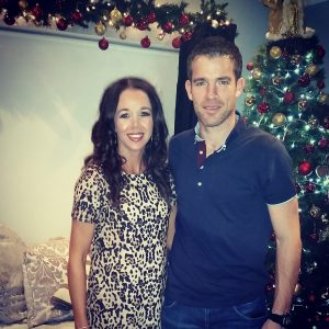 donna with her husband standing at a christmas tree