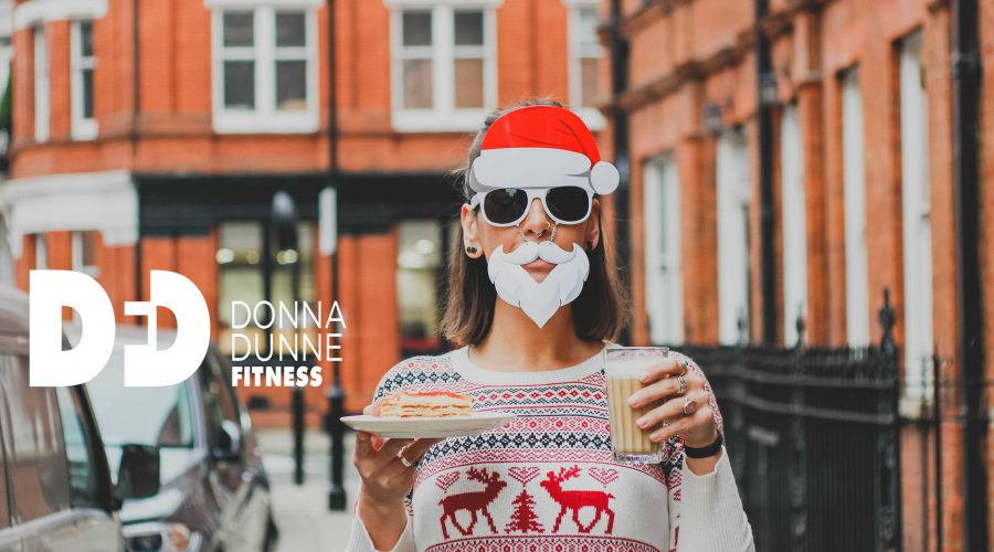 lady dressed in christmas jumper holding food wearing a santa mask and santa hat